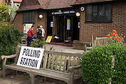Three tellers from the main political parties check the addresses of voters in St. Barnabas Parish Church, Dulwich Village SE21 that serves as a temporary Polling station for voters on Britain's general election day. Their job is to record the election numbers of those about to vote, making sure that their political colleagues don't drop more literature in to that address, now that the occupants have voted.