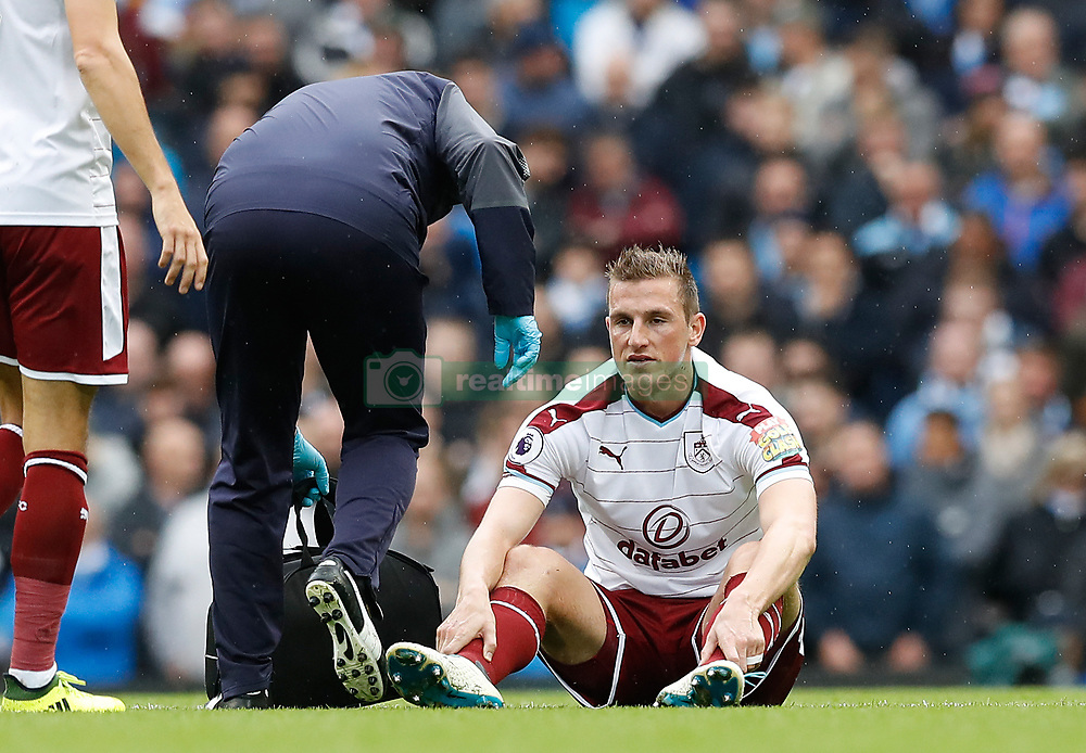 Burnley's Chris Wood sits injured during the Premier League match at the Etihad Stadium, Manchester.