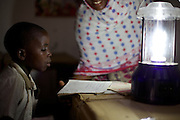 Children learning in the evening thanks to a solar powered lantern...The lanterns are supplied by the Barefoot Solar project which enables women from the poorest communities in rural Tanzania to run successful businesses by installing, repairing and maintaining solar equipment for their communities and beyond...VSO volunteer Lesley Reader project manages the scheme by liaising with the Tanzanian government, Barefoot college and the Indian government.