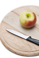 Apple and knife on wooden plate over white background