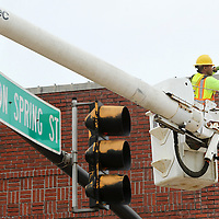 Adam Robison | BUY AT PHOTOS.DJOURNAL.COM<br /> Martin Lumpkin, a worker for Webster Electric, based in Meridian, installs a radio transmitter that will signal all the other red lights to maximize traffic flow downtown on Main Street Wednesday morning in Tupelo.