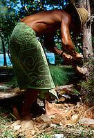 A Polynesian man cracks open a coconut, Moorea, French Polynesia