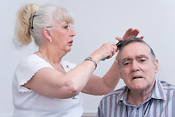 Man with Alzheimer's Disease having his hair combed by his wife whilst she is visiting him at the Nursing Home where he lives,