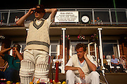 A batsman prepares to walk on to the field during a local club match in Paignton, UK. Adjusting his cap before taking to the field of play, the young man already wears his pads and 'whites' the clothing required of club cricket players on match days. A local company is sponsoring the team or pavilion where members and officials sit enjoying the afternoon's play, ready to cheer on the batsman.