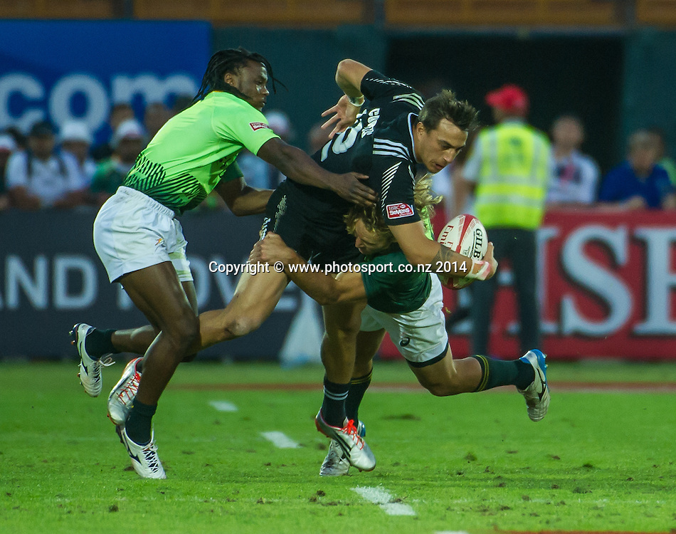 Ambroase Curtis of New Zealand is caught by a couple of South African defenders in the Cup Semi Final of the IRB Sevens World Series rugby tournament at the Emirates Airline Dubai Rugby Sevens in Dubai, UAE, on Saturday, Dec. 6th, 2014. Photo by: Stephen Hindley/Sportdxb/Photosport