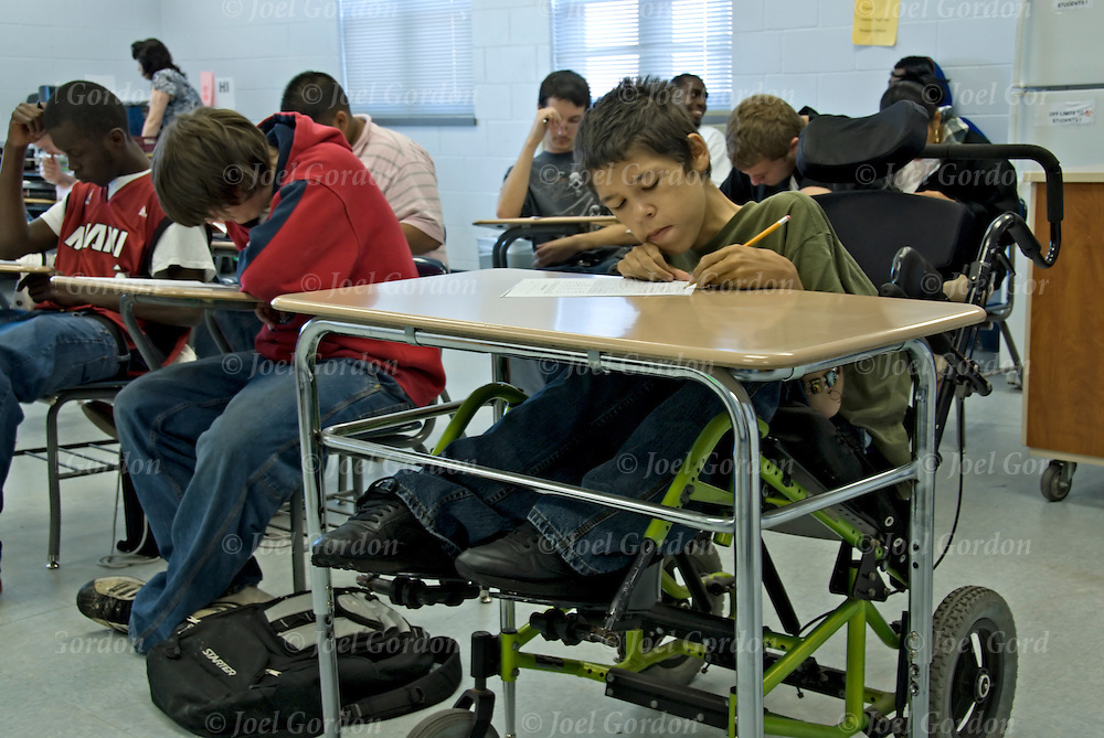 Muscular Dystrophy student mainstreaming taking test in classroom  in wheelchair writing with pencil at table
