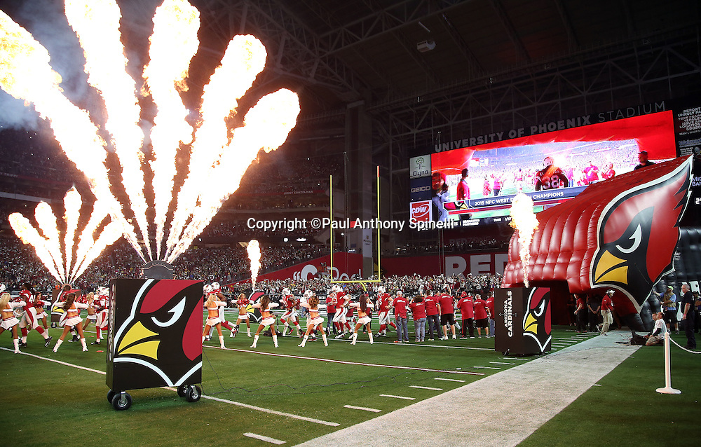 Fire comes out of sideline machines as players run onto the field surrounded by cheerleaders before the Arizona Cardinals NFL NFC Divisional round playoff football game against the Green Bay Packers on Saturday, Jan. 16, 2016 in Glendale, Ariz. The Cardinals won the game in overtime 26-20. (©Paul Anthony Spinelli)