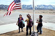 At the end of the day, pupils are pulling down a US flag from its pole, in front of Ibapah Elementary School, in Ibapah, Deep Creek Valley, next to the Goshute Reservation, on the Nevada-Utah border, USA.