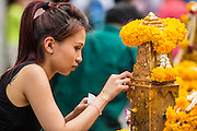 27 SEPTEMBER 2012 - BANGKOK, THAILAND:  A woman applies gold leaf as an offering at the Erawan Shrine in Bangkok. The Erawan Shrine is a Hindu shrine in Bangkok, Thailand, that houses a statue of Phra Phrom, the Thai representation of the Hindu creation god Brahma. A popular tourist attraction, it often features performances by resident Thai dance troupes, who are hired by worshippers in return for seeing their prayers at the shrine answered. The Erawan Shrine was built in 1956 as part of the government-owned Erawan Hotel to eliminate the bad karma believed caused by laying the foundations on the wrong date. The hotel's construction was delayed by a series of mishaps, including cost overruns, injuries to laborers, and the loss of a shipload of Italian marble intended for the building. Furthermore, the Ratchaprasong Intersection had once been used to put criminals on public display. An astrologer advised building the shrine to counter the negative influences. The Brahma statue was designed and built by the Department of Fine Arts and enshrined on 9 November 1956. The hotel's construction thereafter proceeded without further incident. In 1987, the hotel was demolished and the site used for the Grand Hyatt Erawan Hotel.    PHOTO BY JACK KURTZ