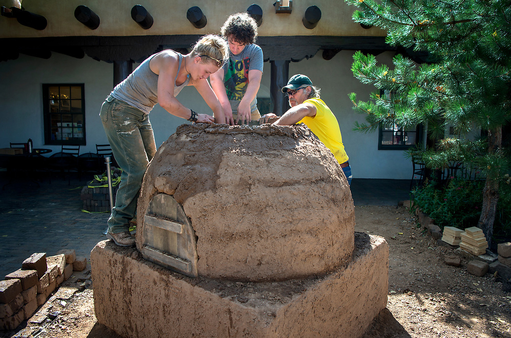 em071917h/jnorth/From left, Leighan Fulfer, from Mountainair and an intern with Corner Stone, Adin Lichtenstein, a volunteer from Santa Fe, and Jeff Davis, from Clovis and a student at at SFCC, build a horno in the courtyard of the Palace of the Governor's in Santa Fe, Wednesday July 19, 2017. (Eddie Moore/Albuquerque Journal)