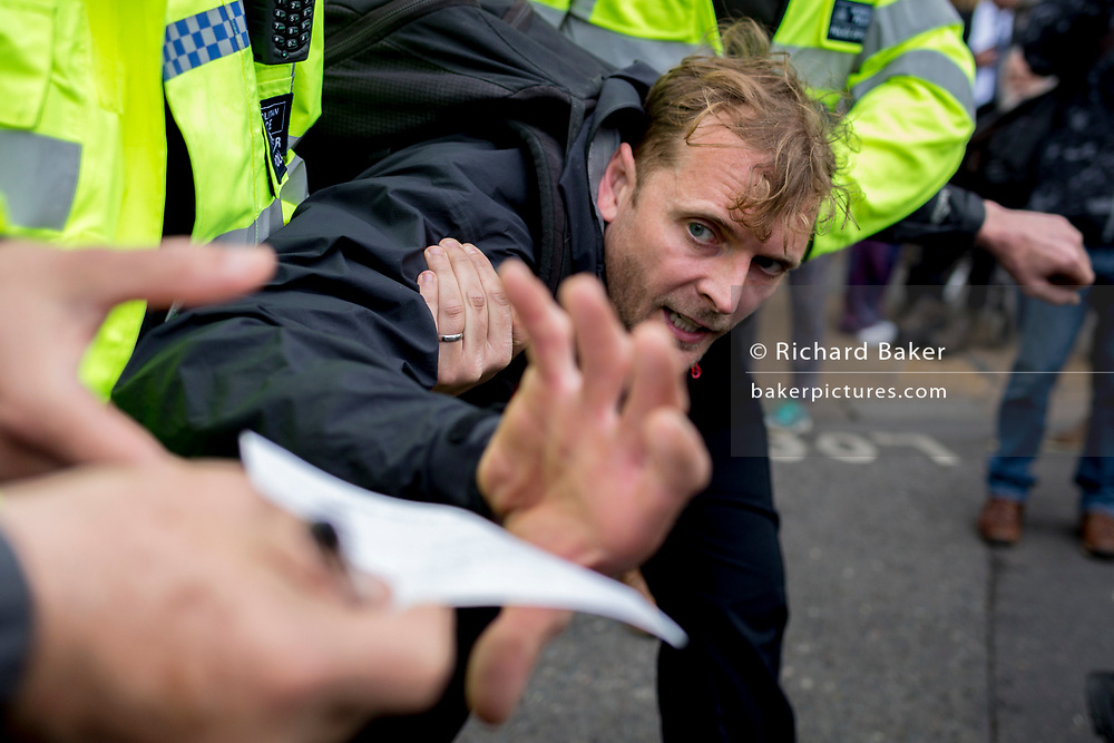 An environmental activist grabs a legal advice leaflet while being arrested under Section 14 of the Public Order Act after blocking the highway at Bank in the City of London on the 11th and final day of protests, road-blockages and arrests across London by the climate change campaign Extinction Rebellion, on 25th April 2019, in London, England.