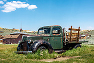 An old green pickup truck with flat bed and wooden rails deteriorates where abandoned at Bodie State Historic Park and ghost town. Grass grows up around its tires.