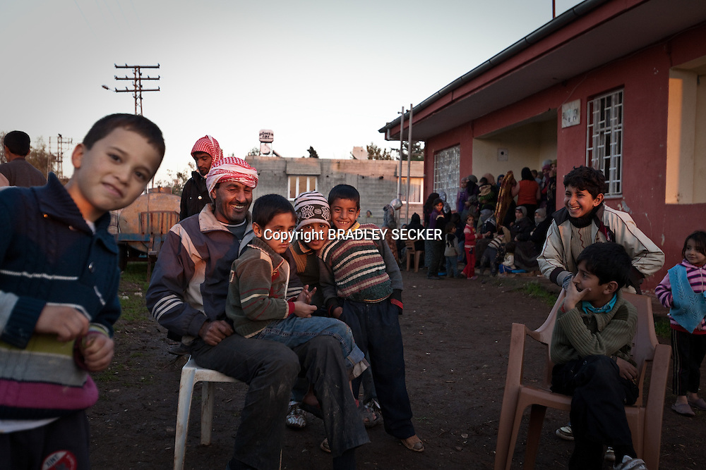Members of the Jasem family in the garden of their temporary home in Davutpasa village, bordering Syria. The extended family of more than 60 people share three bedrooms and very little food in Davutpasa, Turkey. 12/29/2012. Bradley Secker for the Washington Post