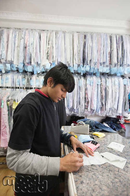 Side view of young man working at dry cleaning shop