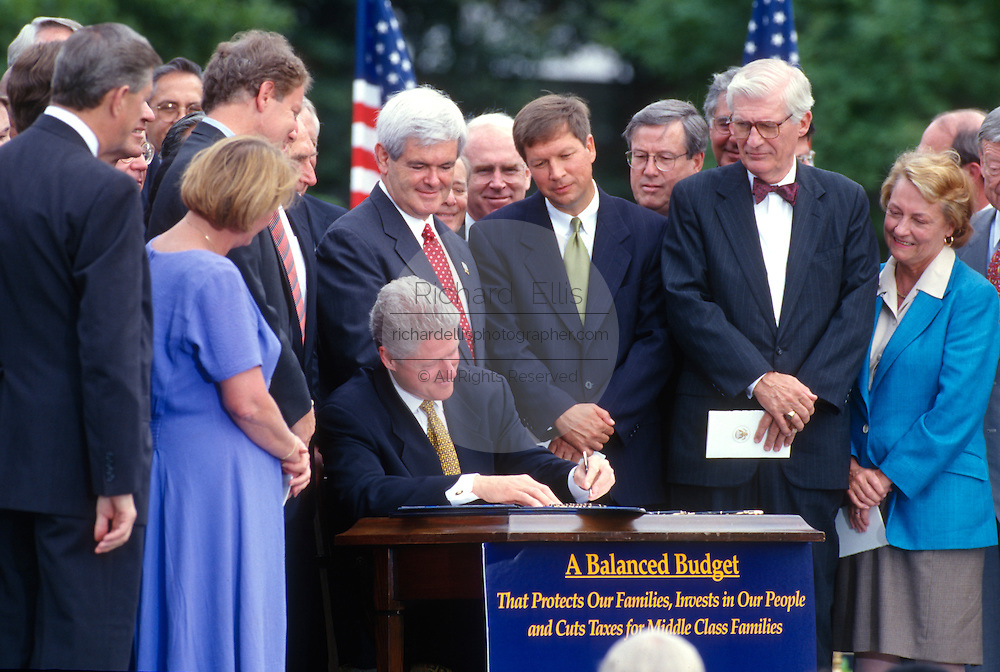 U.S. President Bill Clinton signs into law the balanced budget bill during a ceremony on the South Lawn of the White House August 5, 1997 in Washington, DC.  Congressmen Newt Gingrich, John Kasich and others look on.