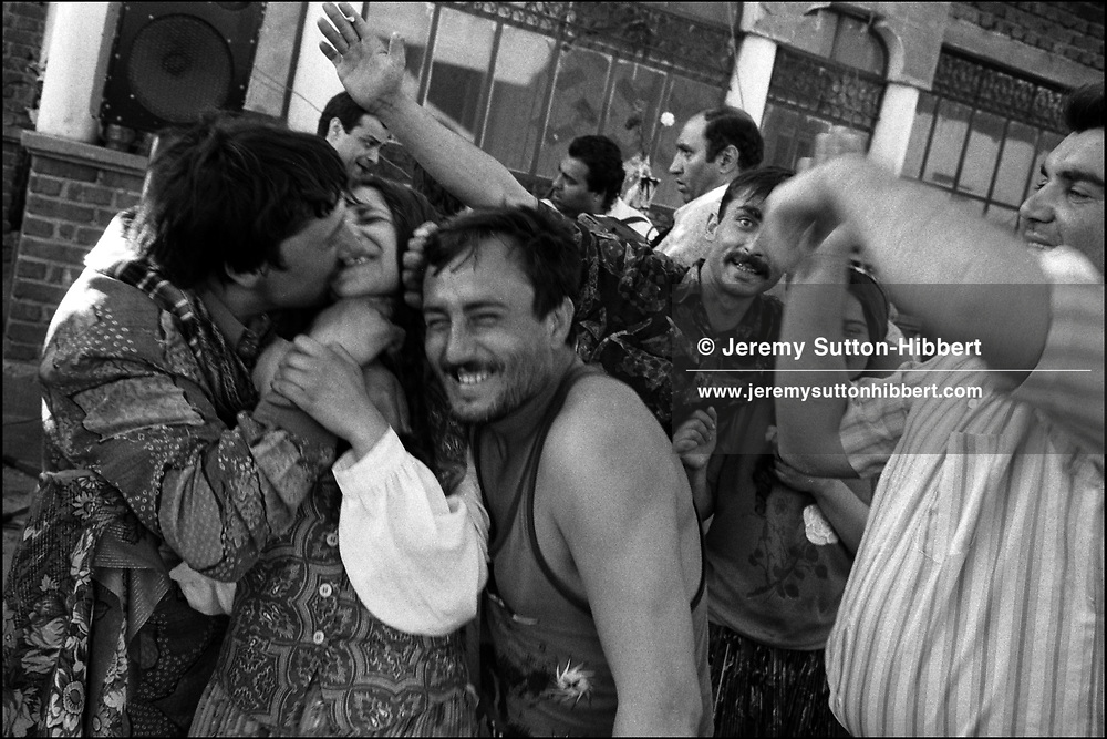 LIULIU GOGU MIHAI TRIES TO KISS CASINCA MIHAI AGAINST HER WISHES DURING THE ROMANIAN ORTHODOX EASTER CELEBRATIONS. SINTESTI, ROMANIA, MAY 1997..©JEREMY SUTTON-HIBBERT 2000..TEL./FAX. +44-141-649-2912..TEL. +44-7831-138817.