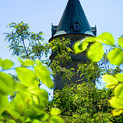 Clocktower of the Musee de la Banque (Bank Musuem) as seen thru the bright green foilage from the gorge below