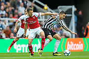 Aaron Ramsey (#8) of Arsenal challenges Joselu (#21) of Newcastle United for the ball during the Premier League match between Newcastle United and Arsenal at St. James's Park, Newcastle, England on 15 September 2018.