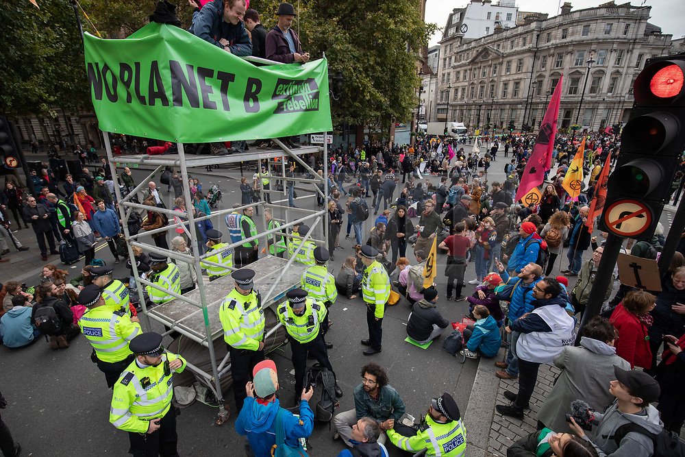© Licensed to London News Pictures. 07/10/2019. London, UK. Climate change activists stage a sit down demonstration in Trafalgar Square, London, closing the road to traffic, as part of a wider two week long demonstration to cause disruption in the capital. The activists are calling for the government to acknowledge and act on climate change. Photo credit : Tom Nicholson/LNP