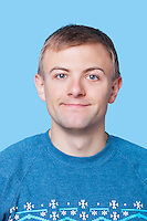 Close-up portrait of young man in sweater against blue background