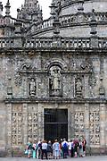 Tourists and tour guide at Quintana de Mortos gate of Cathedral of Santiago de Compostela, Galicia, Spain