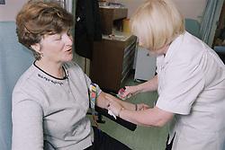 Phlebotomist in Outpatients blood lab taking blood sample,