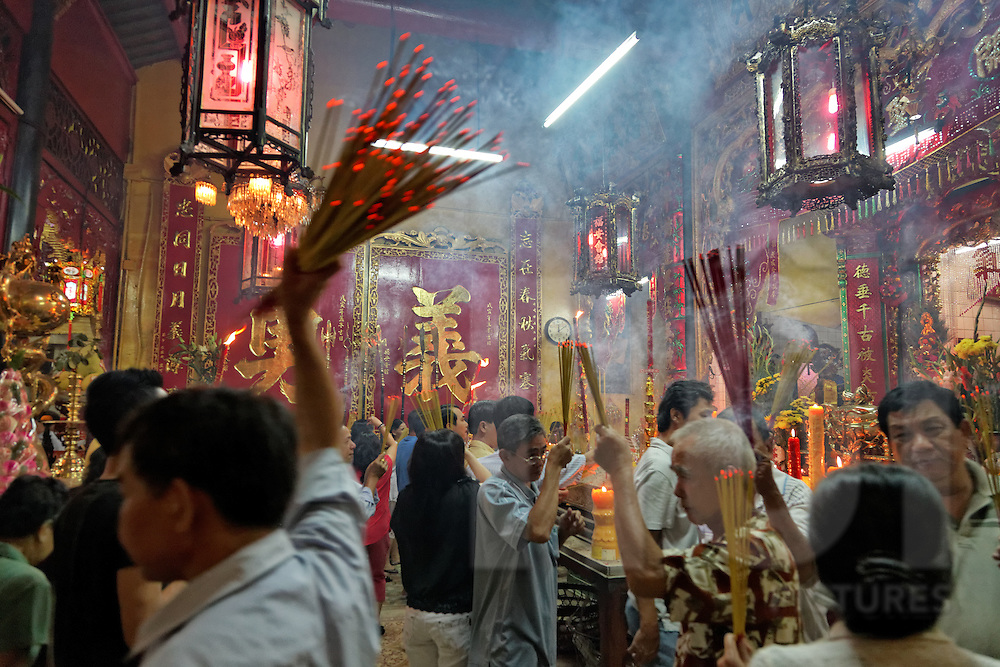 After midnight inside Phuoc An Hoi Quang Pagoda, people scramble to burn incense to fulfill duties and rituals to pray for a prosperous year during the early hours of Tet New Year, Cholon, Ho Chi Minh City, Southeast Asia
