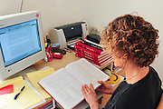 Female Copy-Editor working in front of a computer editing an academic paper with the aid of a dictionary and other textbooks