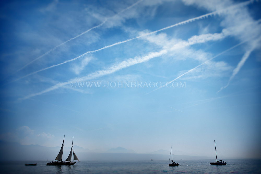 Photo of sailboats on Lake Geneva in Lausanne, Switzerland with a dramatic blue sky above.
