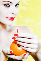 beautiful caucasian woman portrait offering orange juice studio on yellow background