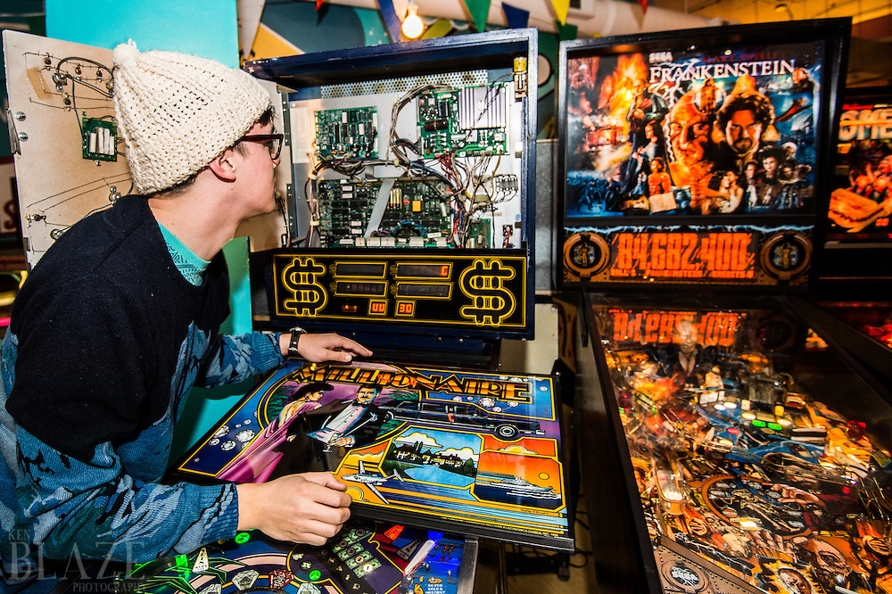 Technician Steve Juchnowski removes the back glass from a pinball machine at the Super Electric Pinball Parlor in the Ohio City neighborhood of Cleveland.