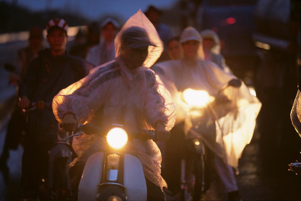 Asia, Vietnam, Hué, Motorcyclists at traffic light in rain on Phu Xuan Bridge across Mekong River