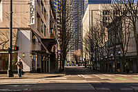 A pedestrian pauses before crossing the empty intersection of Pike Street & 5th Avenue. In this image, he appears to be the only human being in the deserted downtown neighborhood. (March 21, 2020).