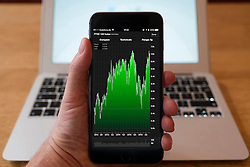 Using iPhone smartphone to display stock market performance chart for FTSE 100 index