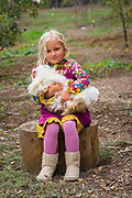 Young blond girl with rooster sitting on a stump in the forest.