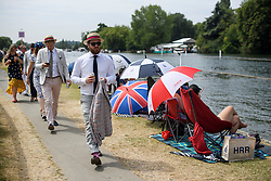 © Licensed to London News Pictures. 04/07/2018. Henley-on-Thames, UK. Men in jackets walk past people lunching on the river banks on Day one of the Henley Royal Regatta, set on the River Thames by the town of Henley-on-Thames in England. Established in 1839, the five day international rowing event, raced over a course of 2,112 meters (1 mile 550 yards), is considered an important part of the English social season. Photo credit: Ben Cawthra/LNP