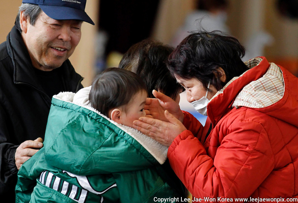 A woman greets a baby as she reunites with her relatives at a shelter for the first time after an earthquake and tsunami in Rikuzentakata in Iwate prefecture, northeast Japan March 15, 2011. /Lee Jae-Won