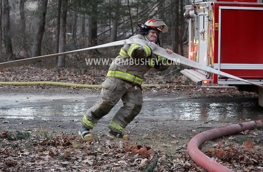 A firefighter pulls a hose to the scene of a structure fire on Bruyn Road in the Town of Shawangunk on Thursday, Jan. 24, 2013.