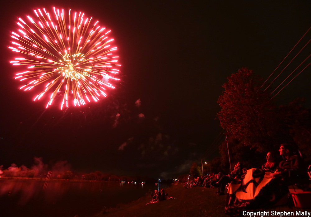 People along the shore enjoy the fireworks during the Cedar Boat Club Venetian Nights Lighted Boat Parade and Fireworks along the Cedar River on Saturday evening, August 18, 2012.
