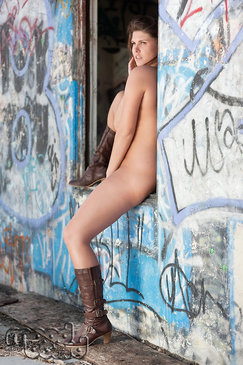 Naked young woman wearing boots as she sits on window sill