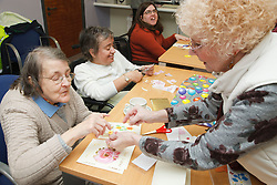 Volunteer assisting a group in craft activity at a resource for people with physical and sensory impairment.