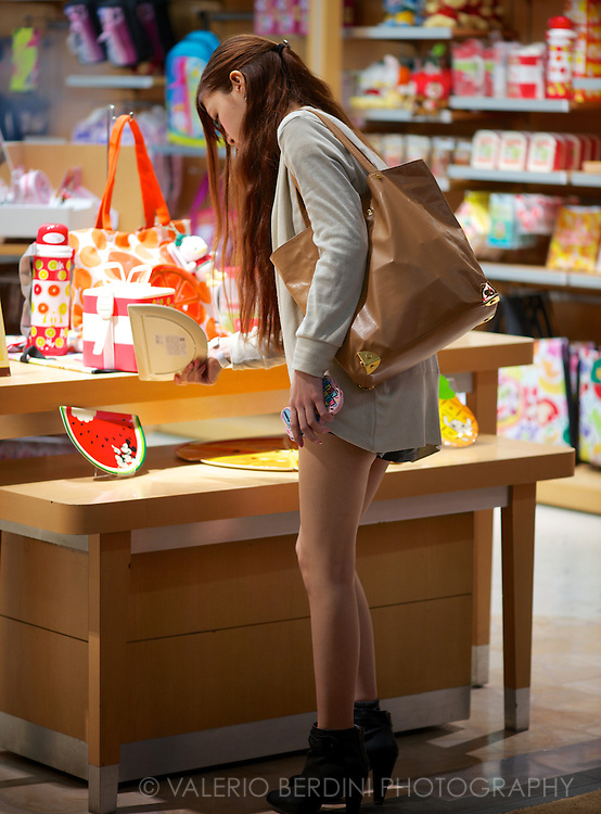 A fashionable girl browse through a shop in the shopping arcade in the Dotonbori district of Osaka.  Japan 2013