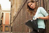 Woman leaning on railing holding open briefcase.