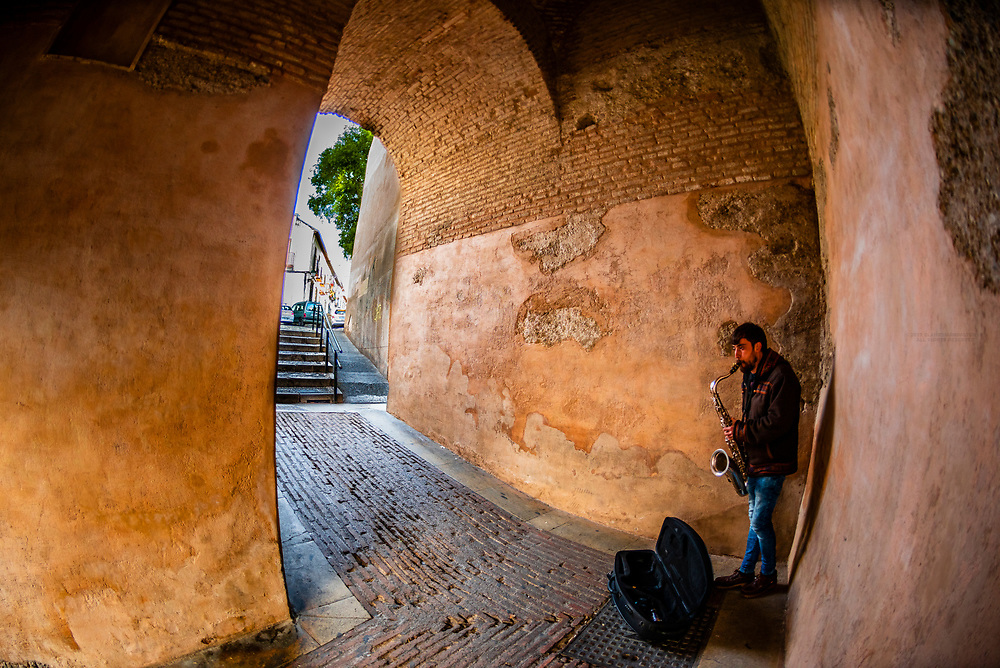 Man playing a saxophone inside the old city wall, Granada, Granada Province, Andalusia, Spain.