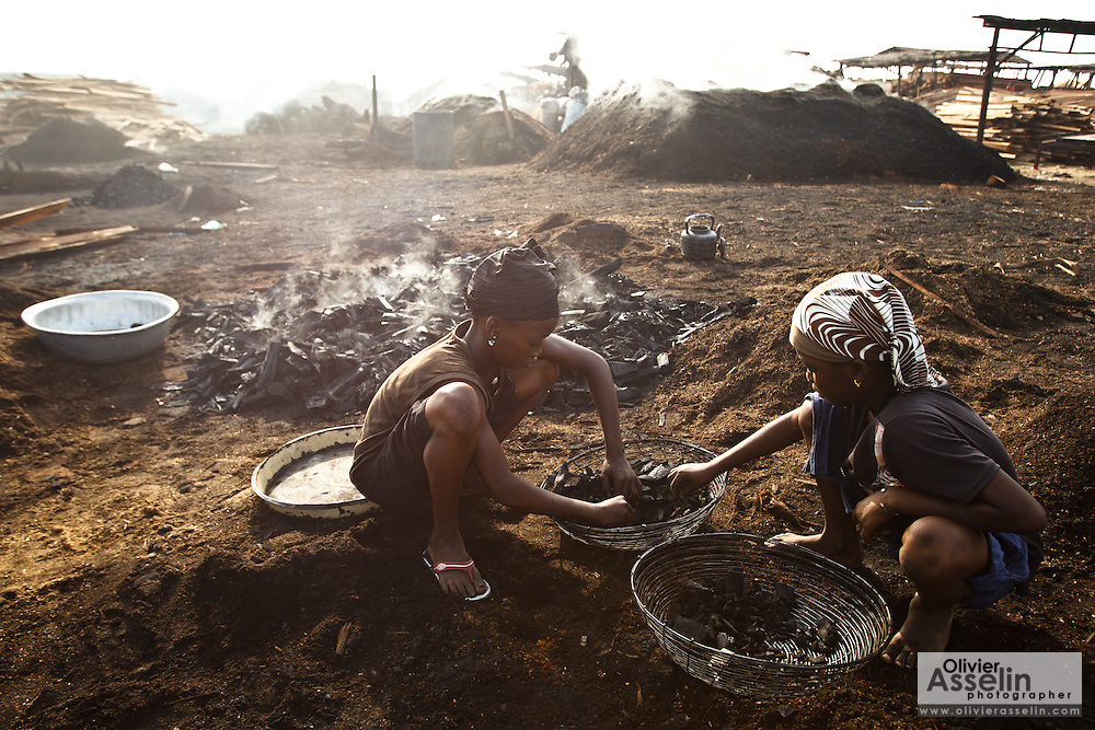 Two girls sort pieces of charcoal at a wood charcoal production site on the outskirts of San Pedro, Bas-Sassandra region, Côte d'Ivoire on Sunday March 4, 2012. Men, women and children - who don't go to school - work here seven days a week.
