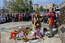 © Licensed to London News Pictures. 11/05/2017. Bradford, UK. Bradford City fan Ryan Exom stands with his hand on the Bradford City Fire memorial sculpture during a ceremony in Bradford to commemorate the 32nd anniversary of the Bradford City fire. The Bradford City fire happened on 11th May 1985 during a game between Bradford City and Lincoln City. The disaster killed 56 and injured at least 265 people. Photo credit : Ian Hinchliffe/LNP