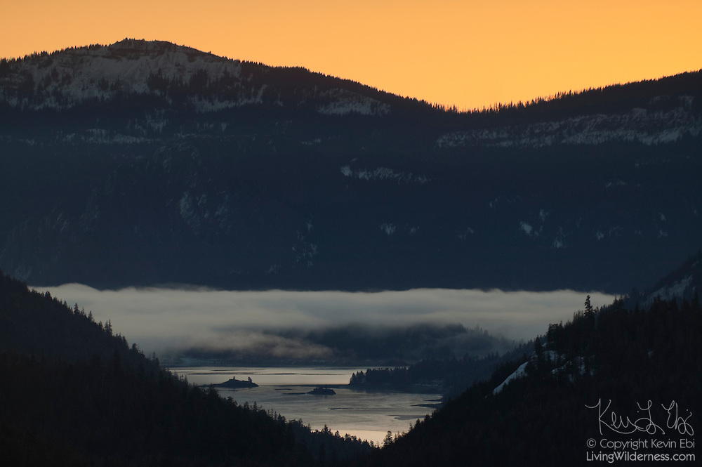 A layer of early morning fog hovers over the partially frozen Clear Lake, located west of White Pass, Washington.