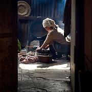 Lao woman preparing meal in simple kitchen (Luang Prabang (Louangphrabang), Laos - Nov. 2008) (Image ID: 081124-0915581a)