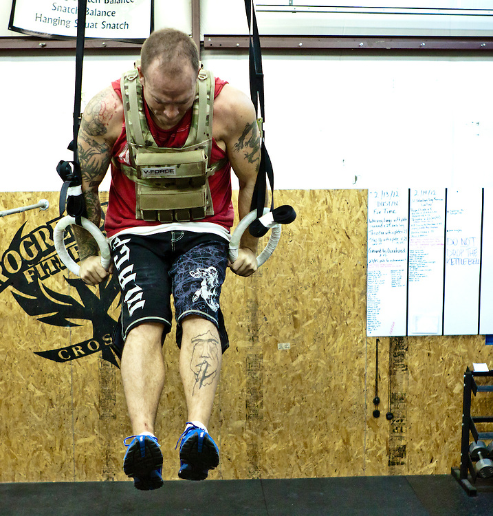 Doug Becker does a muscle up with a weightvest from Weightvest.com at Progressive Fitness CrossFit.