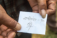 A homeowner from Dolakha, displays his ticket showing he is first in line  to receive an installment of, Rs 50,000 of the promised Rs200,000 to rebuild his home in Dolakha, Nepal  April 13, 2016. Less than one-tenth of a percent, approximately 700 of the 770,000 owners of the affected households, have received cash grants from the government to rebuild their homes.  <br /> Gurkha was one of the hardest hit areas, including the Singati Bazaar, where over 100 bodies were buried under the ruble following the 7.8 magnitude April 25, 2015 earthquake and May 12th aftershock. Singati was the major market for residents of 21 Village Development Committees and many survivors of the April 25th earthquake were in the bazaar buying supplies when the aftershock hit causing a huge landslide.<br /> &copy; 2016 Michelle McLoughlin
